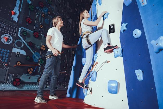 若い女性が室内で岩の壁にロッククライミングを練習します。