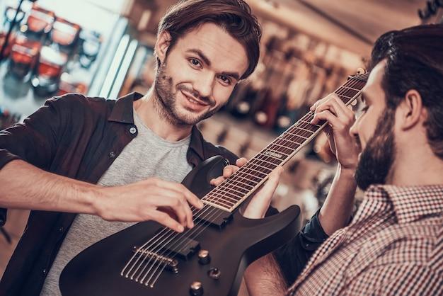 弦楽器の販売人はエレキギターを実演します。