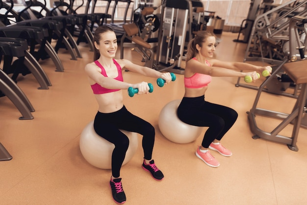Мать и дочь сидит делать упражнения с гантелями.