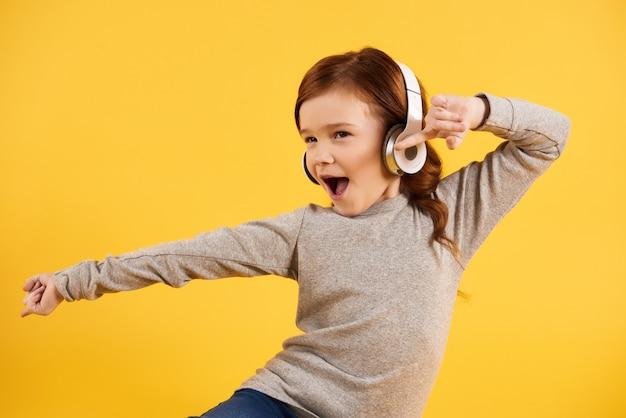 Рыжеволосая активная девушка в наушниках энергично танцует.