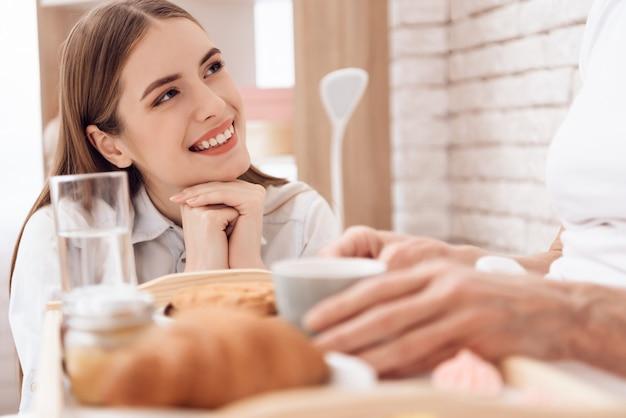 女の子はトレイに朝食をもたらします。女の子は笑っています。
