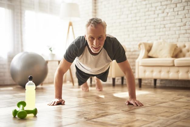Поза упражнение старший мужчина делает планку тренировки.