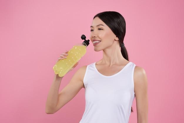 Азиатская девушка позирует с спортивный напиток на розовый.