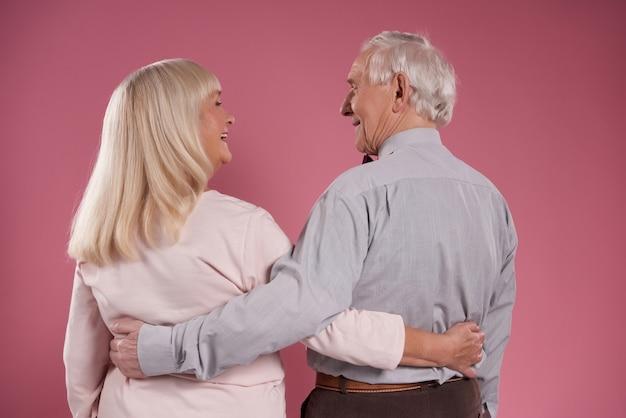 Счастливая пожилая пара обнимает друг друга со спины.