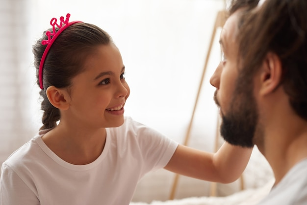 小さな女の子は、ブラシで父親の顔をきれいにします。