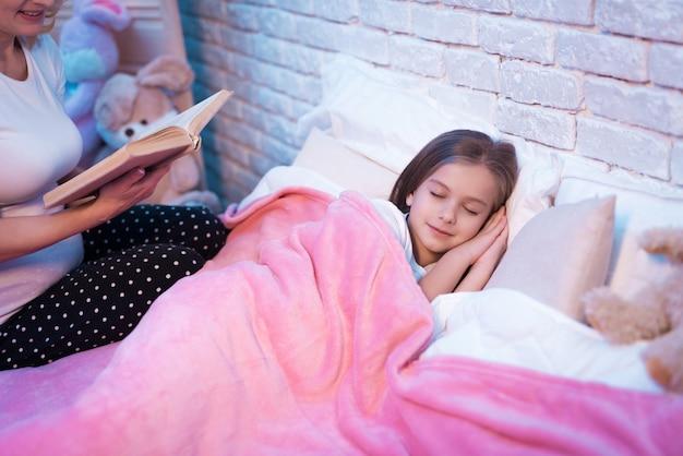 女の子が家に横たわっている間本を読んで祖母。