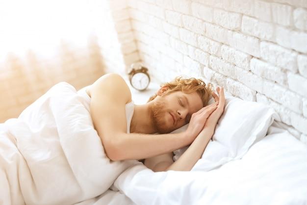 男は白い毛布の下で眠ります。良い夢を。