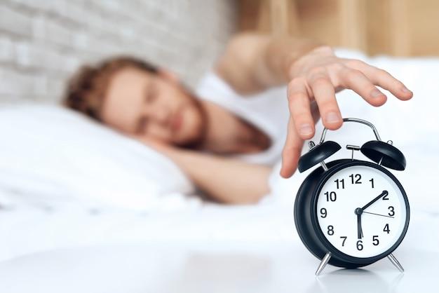 赤毛の若い男が目覚まし時計をオフに手を差し伸べる。