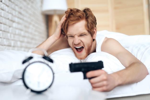 Разбудил злого человека, целится из пистолета в будильник