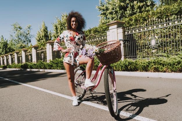 セクシーなムラートの女の子が自転車に立っています。