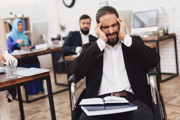 男はオフィスで頭痛を感じて疲れたビジネスマン。