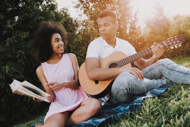 アフリカ系アメリカ人は夏に公園で休んでいます。