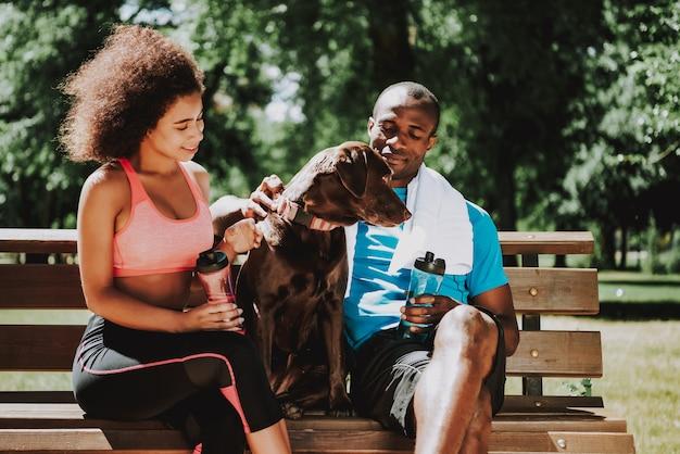 アフリカ系アメリカ人と公園のベンチにかわいい女の子