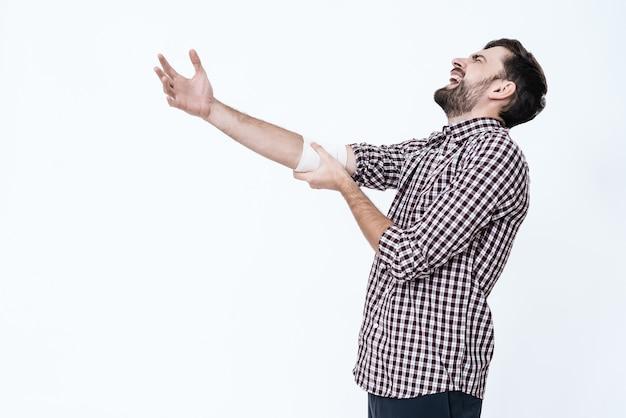 包帯肘を持つ若い男は痛みを感じます。