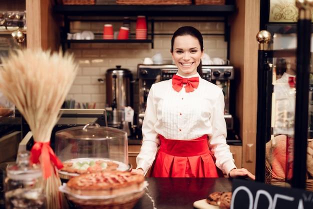 モダンなパン屋に立っている若い笑顔の女性。