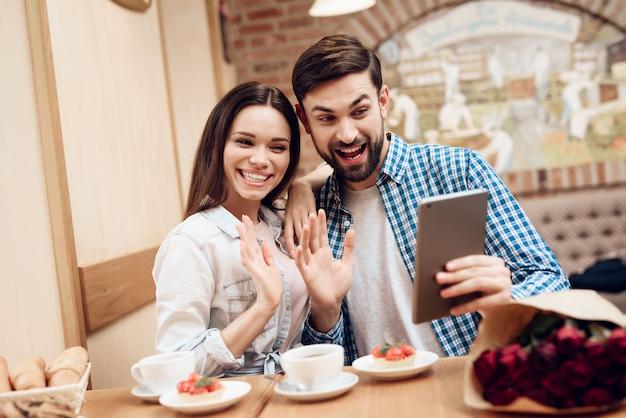 モダンなカフェテリアでタブレットを使用して若いカップル。