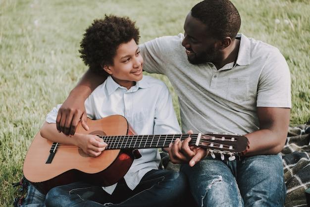 Отец учит своего сына играть на гитаре на пикнике.