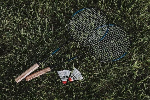 バドミントンラケットと芝生の上の羽根。