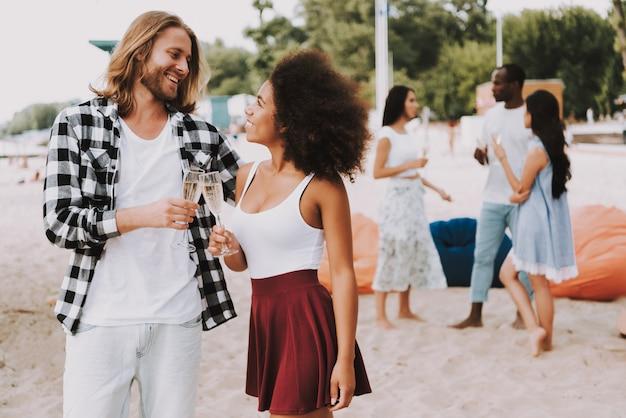 Счастливая пара хипстер, празднуя на берегу летом.