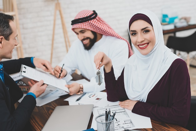 幸せな豊かなアラブのビジネスマンが家の契約に署名します。