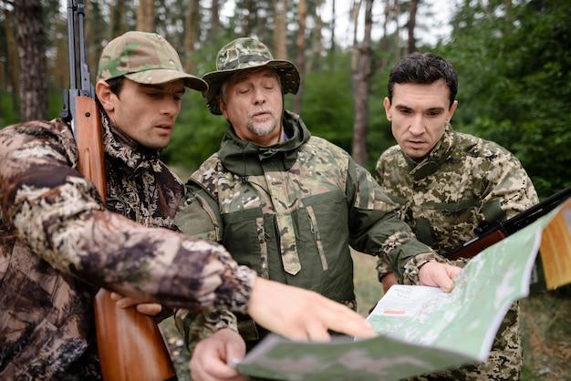 Планирование маршрута в лесу охотники изучают карту походов.