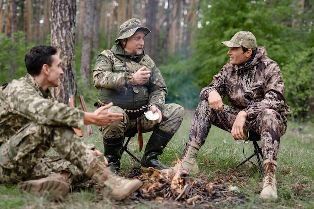 Люди, готовящие на огне охотников, консервы пикник.