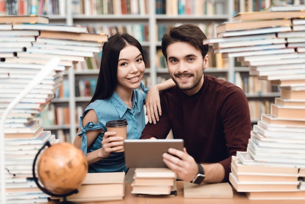 本に囲まれたテーブルに座っている少女と白人の男。