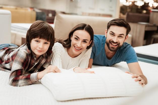 枕に触れるマットレスの上に横たわる若い家族