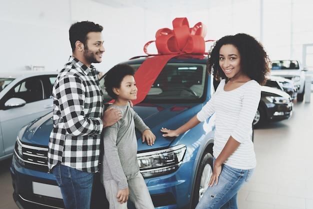 車を選んだ内気な女性は自動車のボンネットに触れます。