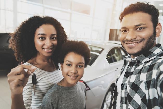 カーリーアフロの女性は車を購入するキー家族を保持しています。