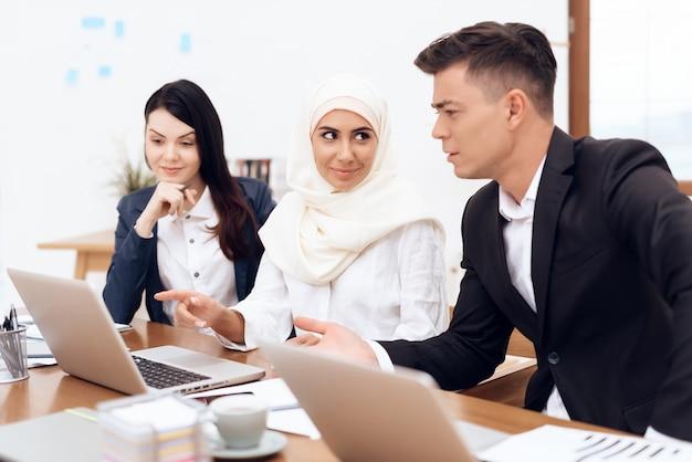 ヒジャーブのアラブの女性は一緒にオフィスで働いています。