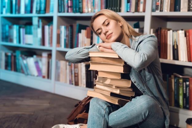 Студент спит с книгами на коленях.