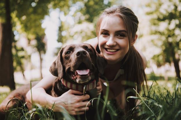 Владелец улыбается и обнимает ее питомца в зеленом лесу.