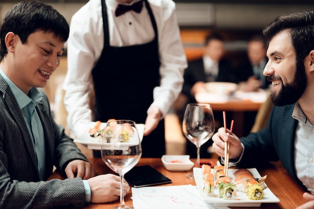 Официант приносит суши к столу.