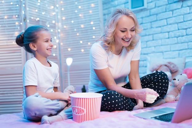 歳の女性と孫娘が映画を見ています