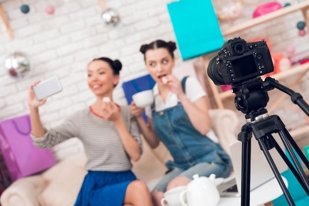 ファッションブロガーの女の子は、カメラにお茶を飲みます。
