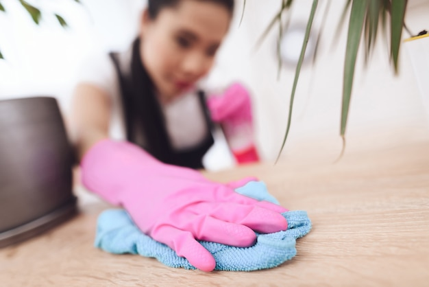 Филиппинская экономка стирает пыль с мебели.