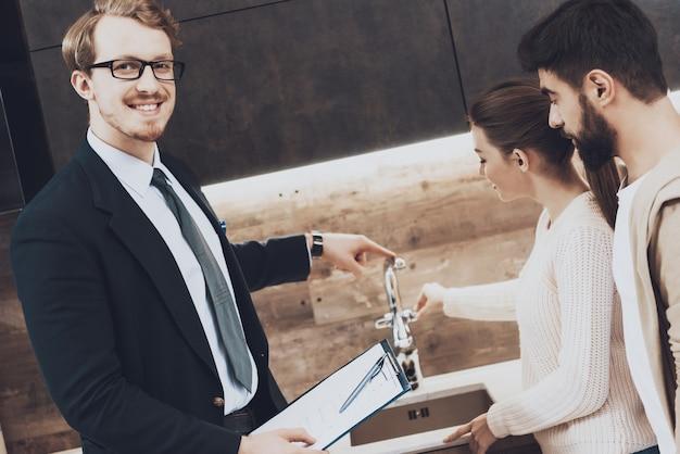 スーツの売り手は、クライアントにキッチンシンクを見せています。