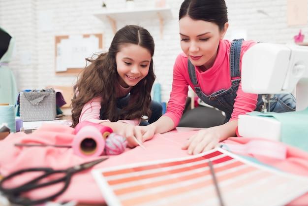 ママと小さな娘は一緒に服を縫います。