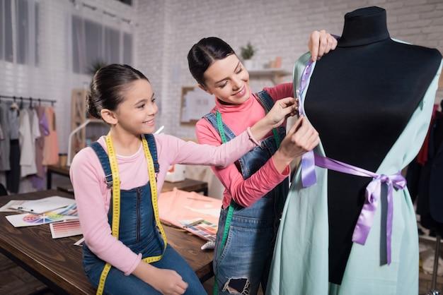 小さな女の子と服を試着している大人の女性