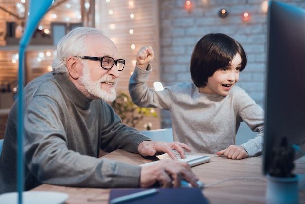 おじいちゃんの孫とコンピューターゲームをプレイ