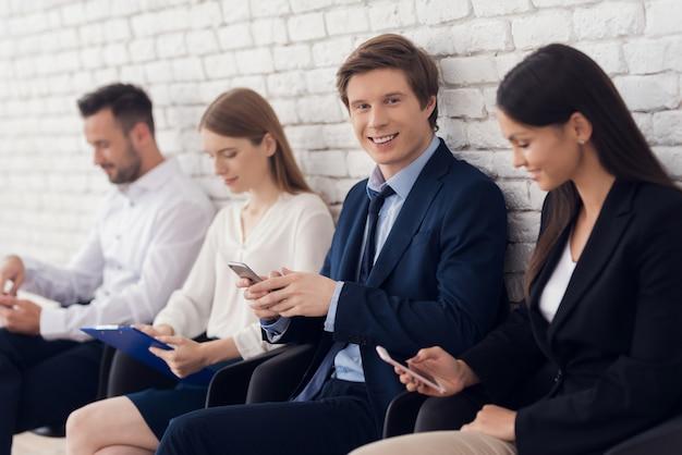 青いスーツの若い自信を持って男は部屋に座っています。
