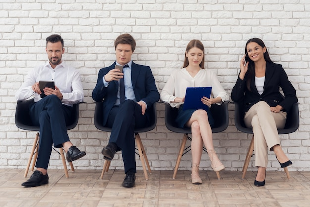 エレガントなスーツの若い同僚が黒い椅子に座っています。