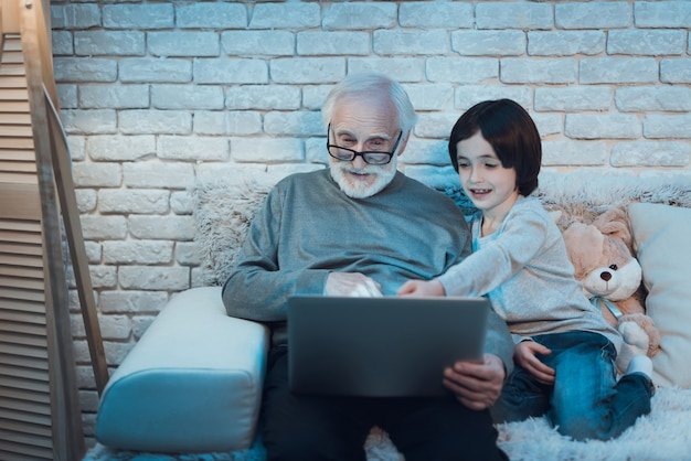 祖父と孫が一緒にラップトップを使用して