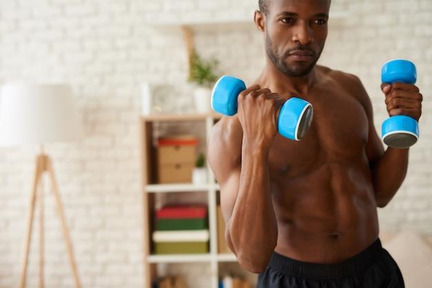 Черный спортсмен накачка мышц гантелями.