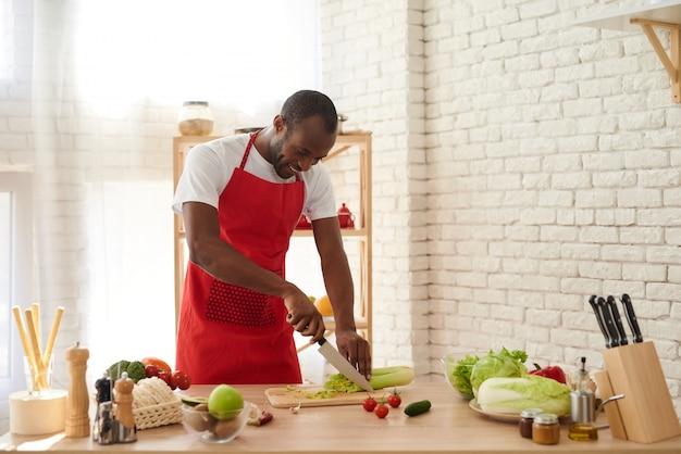 エプロンのアフリカ系アメリカ人は、キッチンでセロリをスライスします。