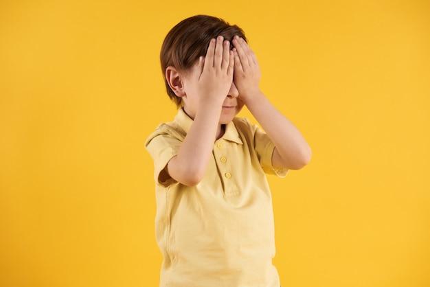 小さな男の子は手で目を閉じます。