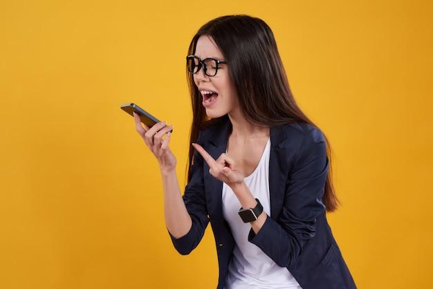 アジアの女の子は分離された電話で叫んでポーズをとっています。