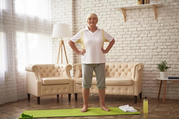 腰に手を家の老婦人でトレーニング。