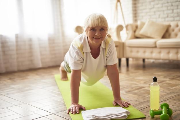 高齢者の女性は、ヨガを練習して板運動をしています。